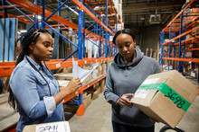 Workers Checking Details On Box In Distribution Warehouse