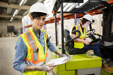 Portrait Of Worker And Forklift Driver In Distribution Warehouse