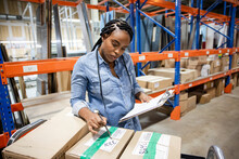 Worker Checking Details On Boxes In Distribution Warehouse