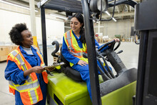 Forklift Driver And Worker Discussing Work In Distribution Warehouse