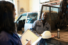 Worker And Driver Talking In Distribution Warehouse