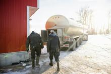 Rear View Of Workers Behind Milk Tanker Truck