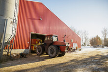 Red Tractor Parked At Entrance Of Barn