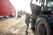 Girl Climbing Into Tractor On Farmyard