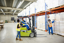 Forklift Driver And Workers Discussing Work In Distribution Warehouse