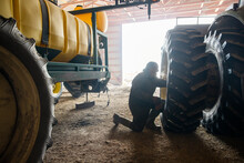 Farmer Fixing Tire Of Tractor In Barn