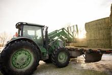 Farmer In Tractor Unloading Haystack From Trailer