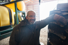 Portrait Of Cheerful Farmer Leaning On Tire In Barn