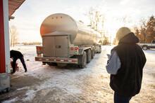 Female Farmer Waiting Behind Milk Tanker Truck