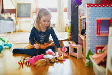 Adorable Toddler Girl Having Fun With Toys In Playroom At Home