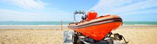 Red Patrol Lifeguard Boat Loaded On A Trailer At The Beach On A Sunny Day. Baltic Sea, Latvia. Transportation, Vacations, Safety, Nautical Vessel, Swimming, Fishing. Panoramic Image