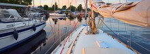 Elegant And Modern Modern Sailing Boats (for Rent) Moored To A Pier In A Yacht Marina At Sunset. Transportation, Cruise, Leisure Activity, Sport And Recreation Theme. Sweden