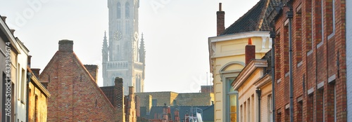 Fotografia Low angle view of a medieval bell tower (Belfry of Bruges) in a historical city center at sunset