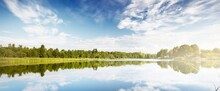 Lake Shore Against A Clear Blue Sky, Green Forest In The Background. Latvia. Symmetry Reflections On The Water, Natural Mirror. Idyllic Summer Rural Scene