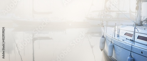 Sailing boats moored to a pier in a thick white morning fog at sunrise, close-up. Yacht club in Kiel, Germany. Sport, recreation, transportation theme - fototapety na wymiar