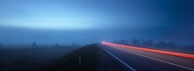 Panoramic View Of The Empty Highway Through The Fields In A Fog At Night. Moonlight. Sunrise. Europe. Transportation, Logistics, Travel, Road Trip, Freedom, Driving. Motion Blur Effect. Rural Scene