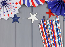 Decorations For 4th Of July Day Of American Independence, Flag, Candles, Straws, Paper Fans. USA Holiday Decorations On A Blue Background, Top View, Flat Lay