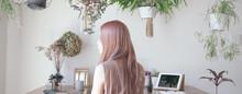 観葉植物に囲まれた、綺麗な髪の女性の後ろ姿