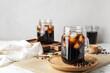Leinwandbild Motiv Mason jars of tasty cold brew and coffee beans on white background