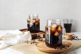 Fototapeta Kawa jest smaczna - Mason jars of tasty cold brew and coffee beans on white background