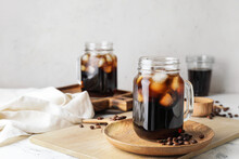 Mason Jars Of Tasty Cold Brew And Coffee Beans On White Background
