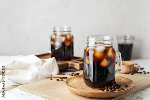 Mason jars of tasty cold brew and coffee beans on white background - fototapety na wymiar