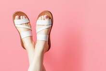 Female Legs In Summer Flip Flops On Pink Background, Copy Space
