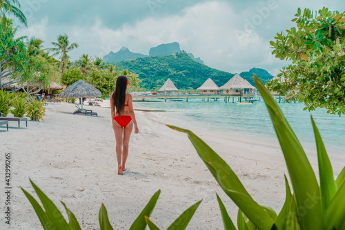 Beach travel vacation luxury hotel in Bora Bora island, Tahiti, French Polynesia. Bikini model walking relaxing on beach, view from behind. Natural beauty nature landscape. - fototapety na wymiar