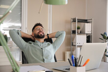 Businessman Relaxing In Office Chair At Workplace