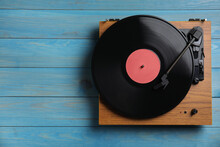 Modern Vinyl Record Player With Disc On Blue Wooden Background, Top View. Space For Text