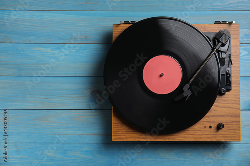 Fototapeta Modern vinyl record player with disc on blue wooden background, top view