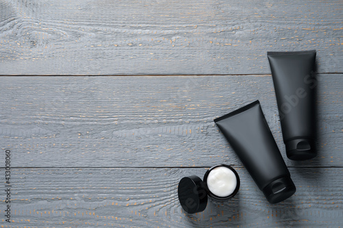 Tubes and jar with men's facial creams on grey wooden table, flat lay. Mockup for design - fototapety na wymiar