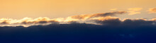 Evening Sunset Panorama With Dark Blue Clouds And Orange Light Clouds.