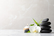 Spa Stones, Bamboo Sprout, Burning Candle And Beautiful Orchid Flower On White Marble Table, Space For Text
