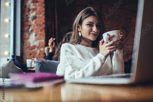 Obraz Satisfied woman drinking coffee in cafeteria - fototapety do salonu