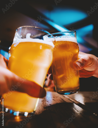 Closeup view of a two glass of beer in hand. Beer glasses clinking in bar or pub - fototapety na wymiar