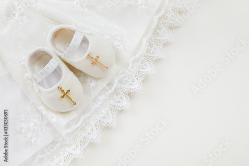 Fototapeta Christening background with baptism baby dress, shoes, and cross on pastel backg