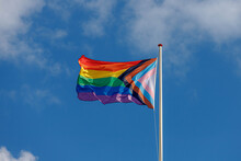 Progress Pride Flag (new Design Of Rainbow Flag) Waving In The Air With Blue Sky, Celebration Of Gay Pride, The Symbol Of Lesbian, Gay, Bisexual And Transgender, LGBTQ Community In Netherlands.