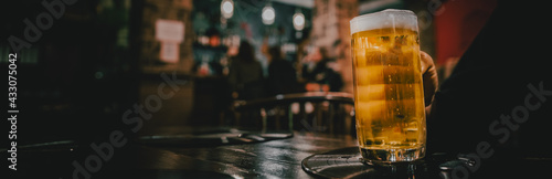 Photo man hold a glass of beer in his hand at the bar or pub