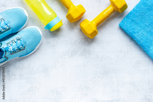 Top view of fitness accessories with dumbbells and sneakers - fototapety na wymiar