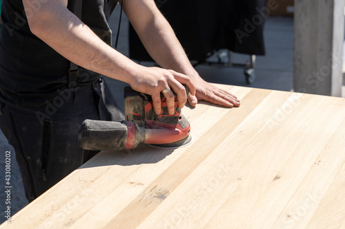 Obraz construction worker using a cordless power sander to sand a massive wooden table top - fototapety do salonu