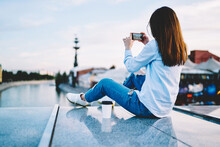 Young Millennial Woman Using Smartphone Application For Making Photo While Resting At Urban Setting, Back View Of Female Hipster Blogger In Casual Wear Shooting Video On Digital Mobile Phone
