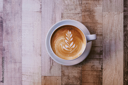 Valokuva A cup of fresh delicious italian cappuccino coffee with latte art in the shape of leaf on wooden background, top view