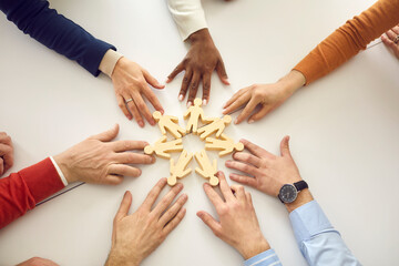 Group of diverse people arrange human figures in circle. Team of multiethnic business partners join little wooden figures on table. Teamwork, community, working together and cooperation metaphor