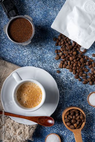 Obraz Top view of a cup of coffee, a coffee container, and a pile of coffee beans on a kitchen table - fototapety do salonu