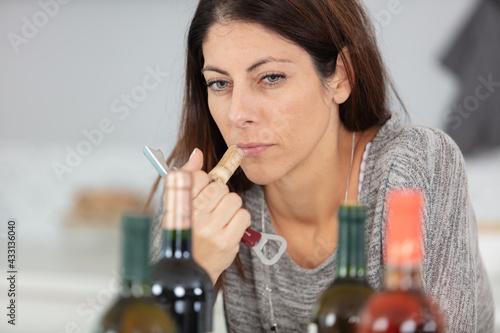 Obraz serious lady smelling wine cork - fototapety do salonu