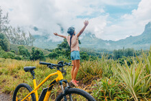 Mountain E Biking Happy Girl With Arms Up Of Happiness Traveling On Tahiti Island With E-bike Riding Electric Mtb Bicycle On Trail Adventure. Travel Summer Lifestyle.