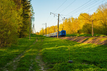 The Back Of A Departind Train, A Path Along The Railway, Spring Landscape. Farewell View.