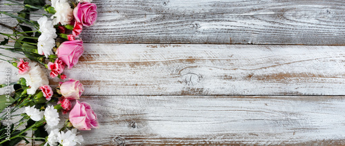 Left border of real bouquet flowers on rustic wooden planks for mothers day or valentines holiday - fototapety na wymiar