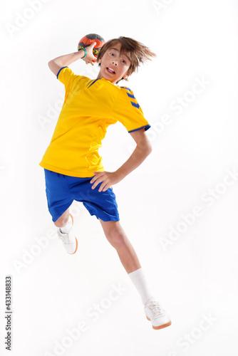 Fotografia Full length photo of a young sporty boy throwing handball to the camera,